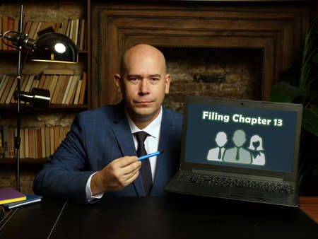 Business concept meaning Filing Chapter 13 with sign on card in hand.