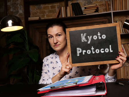 A handsome businesswoman showing a black piece of paper with sign Kyoto Protocol.