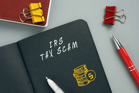 Business concept about IRS TAX SCAM with phrase on the piece of paper. IRS impersonation scams involve scammers targeting American taxpayers by pretending to be IRS collection officers