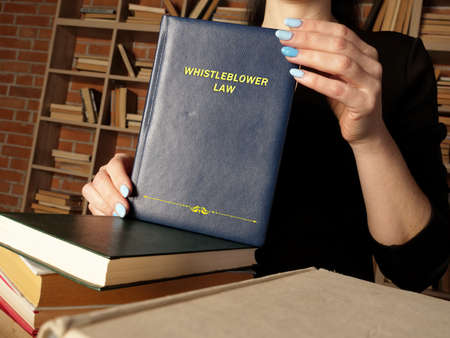 Attorney holds WHISTLEBLOWER LAW book. As a whistleblower you're protected by law - you should not be treated unfairly or lose your job because you 'blow the whistle' Stock Photo