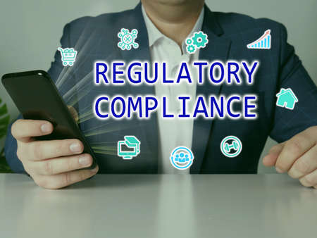 REGULATORY COMPLIANCE phrase on the screen. Bookkeeping clerk use cell technologies at office. Stock Photo