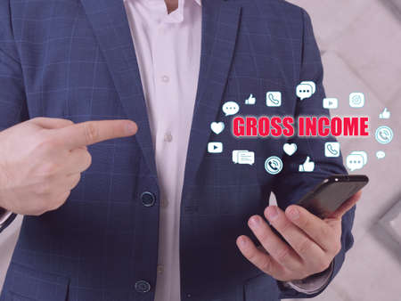 GROSS INCOME text in search bar. Businessman looking at cellphone. Gross income represents the total income from all sources, including returns, discounts, and allowances
