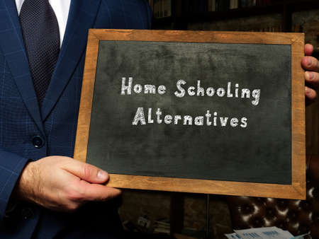 Financial concept about Home Schooling Alternatives with sign on chalkboard in hand. Stock Photo