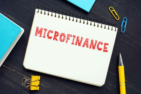 MICROFINANCE phrase on the piece of paper. A banking service provided to unemployed who otherwise would have no other access to financial services