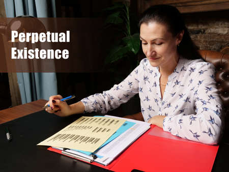 Legal concept about Perpetual Existence Female office workers with yellow shirt holding and writing documents on office desk