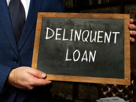 DELINQUENT LOAN text in search line. Broker looking at smartphone.