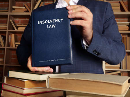 INSOLVENCY LAW book in the hands of a attorney. Insolvency law is the legislation and statutory guidelines by which an insolvency professional shall act