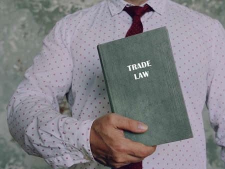 TRADE LAW book in the hands of a lawyer. The rise in prominence of trade law following the creation of the World Trade Organization Stock Photo
