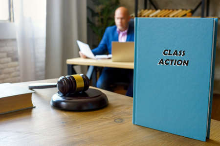 CLASS ACTION book in the hands of a attorney. A class action, also known as a class-action lawsuit, class suit, or representative action
