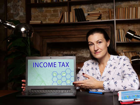 INCOME TAX text in search bar. Manager looking for something at cellphone. INCOME TAX concept. Aa type of tax that governments impose on income generated by businesses and individuals within their jurisdiction