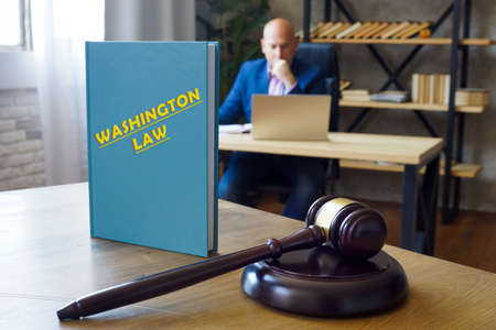 WASHINGTON LAW book in the hands of a jurist. Washington residents are subject to Washington state and US federal laws