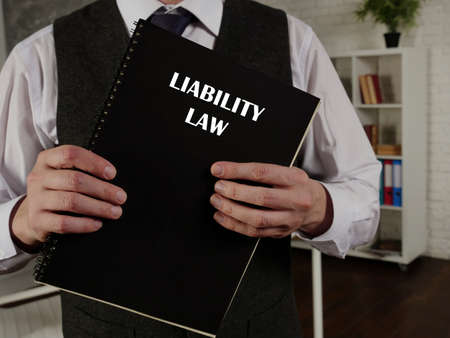 LIABILITY LAW book in the hands of a lawyer. Legal liability concerns both civil law and criminal law and can arise from various