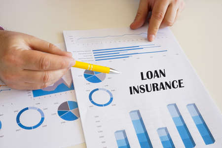 Business concept about LOAN INSURANCE with sign on the chart sheet.