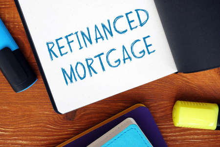 Financial concept meaning REFINANCED MORTGAGE exclamation marks with phrase on the sheet. Stockfoto