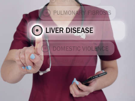 LIVER DISEASE text in menu. Cardiologist looking for something at cellphone. Stockfoto