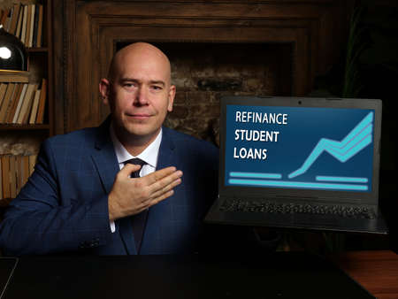 REFINANCE STUDENT LOANS phrase on the screen. Budget analyst use internet technologies at office. Concept search and REFINANCE STUDENT LOANS.