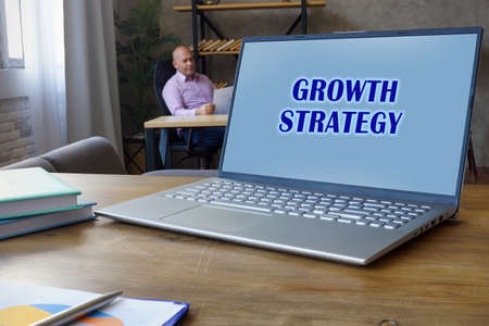 Business concept meaning GROWTH STRATEGY with phrase on the Compact laptop A successful Accountant with documents on the background Stockfoto