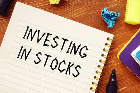 Financial concept about INVESTING IN STOCKS question marks with phrase on the sheet.