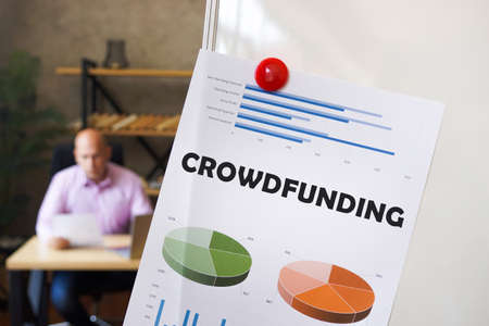 Financial concept about CROWDFUNDING with inscription on the printout with diagrams and tables. A successful businessman with documents on the background