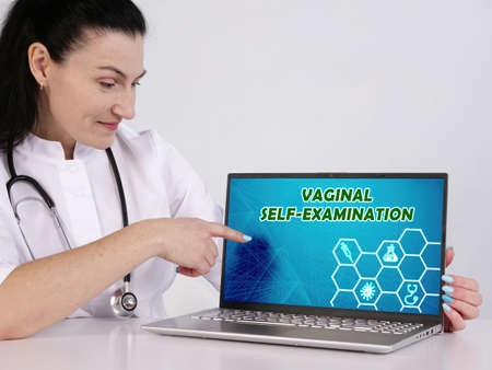 VAGINAL SELF-EXAMINATION inscription on the screen. woman therapist looking at screen of laptop