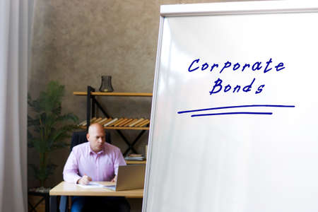 Business concept meaning Corporate Bonds with inscription on the White Marker Writing Board. Businessman working with documents in the background.