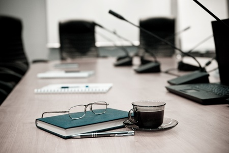 A close-up of a conference room showing a chairs, a table, a coffee cup,  and a note pad. Sharp focus on the cup.