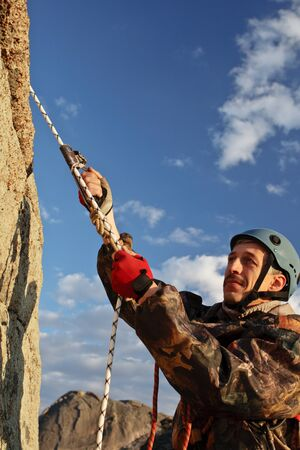 The rock-climber in helmet moves on top Stock Photo - 10470193