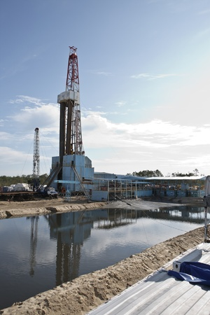 Rig against pit with mud and cuttings photo