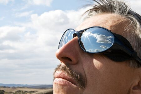 Close up sun glasses of man with the reflection of the clouds Stock Photo - 10842593