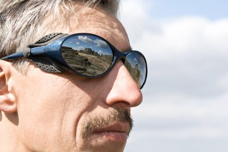 Close up sun glasses of man with the reflection of the mountains Stock Photo - 10842606