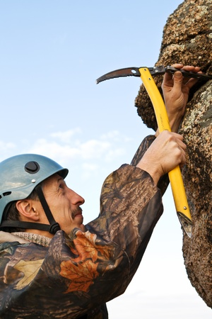 The rock-climber in helmet with ice axe in hands against the sky Stock Photo - 10842604