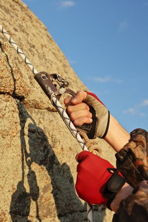 Hands the rock-climber with rope and equipment climbs on top Stock Photo - 10842620