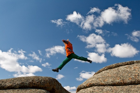 The person jumping on background blue sky in mountains