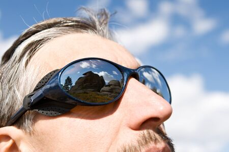 Close up sun glasses of man with the reflection of the mountains Stock Photo - 10878511