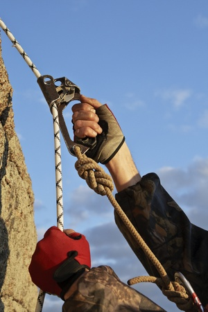 non moving activity: Hands the rock-climber with rope and equipment climbs on top