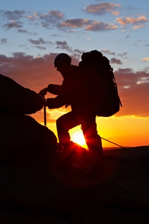 The climber goes uphill on sunset Stock Photo - 10878508