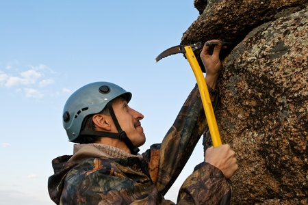 The rock-climber in helmet with ice axe in hands against the sky Stock Photo - 10943731