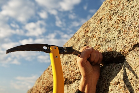 Work of the rock-climber against the sky and mountains