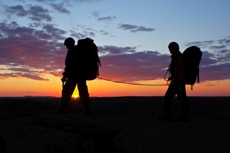 Two climbers walk on sunset's background photo