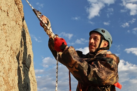 The climber climbs uphill with equipment Stock Photo - 10994265