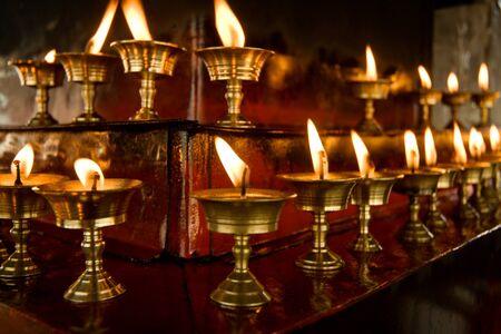 Buddhist butter lamps in Tibetan temple dark Standard-Bild