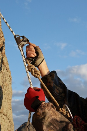 Hands the rock-climber with rope and equipment climbs on top