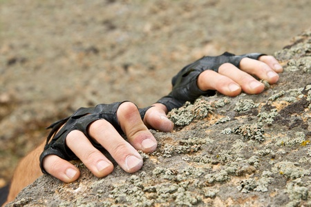 Hands of the climber hanging on rock. Finger are covered by talc.