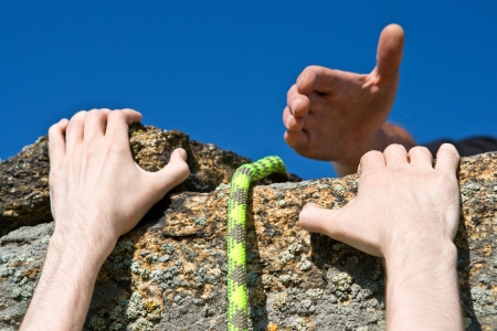 climbing mountain: Hands of climber on brink of rock needing the help