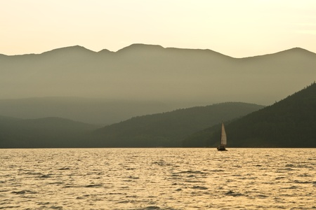 Small sailing yacht sailing on Lake Baikal on the background of dark mountains photo