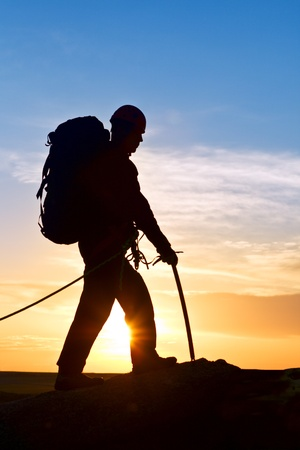 Silhouette climber with an ice axe at mountain top Stock Photo