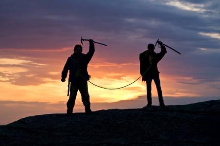 bergbeklimmen: Twee klimmers in de top tegen zonsondergang