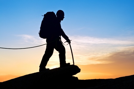 The rock-climber walking on mountain top on decline
