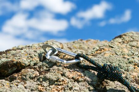 Carbine and hook with rope in stone. Outdoor
