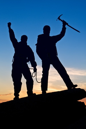 reached: Two travelers reached tops on sunset background Stock Photo